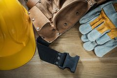 Leather construction belt protective gloves building helmet on w Royalty Free Stock Image