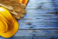 Leather construction belt safety gloves hard hat on blue wooden. Board royalty free stock image