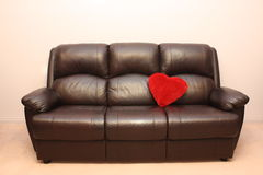 Leather couch with heart. Red heart-shaped pillow on a dark leather couch Stock Image