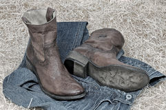 Leather cowboy boots and jeans on straw Royalty Free Stock Images