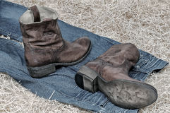 Leather cowboy boots and jeans on straw Royalty Free Stock Image