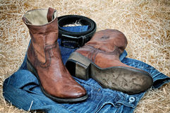 Leather cowboy boots leather belt and jeans on straw. Pair of traditional leather cowboy boots blue jeans and leather belt curtailed into a ring on straw. Retro royalty free stock photos