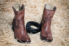 Leather cowboy boots leather belt and jeans on straw. Pair of traditional leather cowboy boots blue jeans and leather belt curtailed into a ring on straw. Retro stock photos