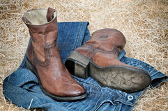 Leather cowboy boots leather belt and jeans on straw. Pair of traditional leather cowboy boots blue jeans and leather belt curtailed into a ring on straw. Retro royalty free stock photo