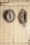 Leather cowboy hat hanging on an old door stock image
