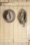 Leather cowboy hat hanging on an old door. Leather cowboy hat and rope hanging on an old weathered door Stock Image