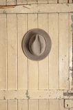 Leather cowboy hat hanging on an old door Royalty Free Stock Photography