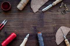 Leather craft accessories. Tools and matherials on dark wooden background top view copyspace Royalty Free Stock Photo
