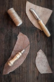 Leather craft accessories. Tools and matherials on dark wooden background top view Stock Photos