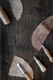 Leather craft. Knife, awl and other tools on dark wooden background top view copyspace Royalty Free Stock Photography