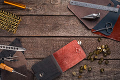 Leather craft or leather working. Leather working tools and cut out pieces of leather on work desk . Leather craft or leather working. Leather working tools and Royalty Free Stock Photos