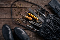 Leather craft or leather working. Leather working tools and cut out pieces of leather on work desk . Leather craft or leather working. Leather working tools and Royalty Free Stock Images