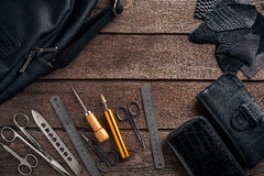 Leather craft or leather working. Leather working tools and cut out pieces of leather on work desk . Leather craft or leather working. Leather working tools and Royalty Free Stock Image