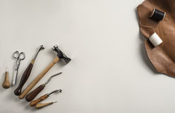 Leather craft tools. On white background with medium brown vegetable tanned cowhide Stock Images