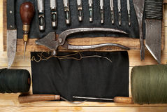 Leather craft tools on wooden background. Craftmans work desk . Piece of hide and handmade tools. Top view. Leather craft tools on a wooden background. Craftmans stock photography