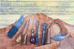 Leather craft tools on a wooden background. Leather craftmans work desk . Piece of hide and working handmade tools on a Stock Photo