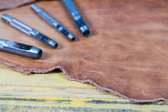 Leather craft tools on a wooden background. Leather craftmans work desk . Piece of hide and working handmade tools on a work table Stock Photography