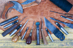 Leather craft tools on a wooden background. Leather craftmans work desk . Piece of hide and working handmade tools on a work table Royalty Free Stock Photography