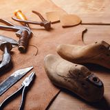 Leather craft tools on wooden background. Workplace for shoemaker. Piece of leather. Cobbler workplace with tools, leather and sho. Es last. Small shoemaker stock photos