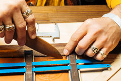 Leather craft for wallet working with tool on leather craftman`s work desk. Hand-made with a hard material royalty free stock photography