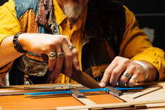 Leather craft for wallet working with tool on leather craftman`s work desk. Hand-made with a hard material stock photos