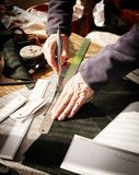Leather craftsman. Cutting a piece of leather with a knife royalty free stock photos