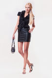 Leather dress. Blond girl in black leather dress, pocketbook Royalty Free Stock Photo