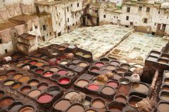 Leather dyeing and tannery pits, Fez, Morocco. Traditional leather dyeing and tannery pits in Fez, with piles of tanned and dyed hides and hides hanging out to Royalty Free Stock Photos