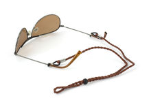 Leather eyeglass cord attached to sunglasses. A new braided leather eyeglass cord attached to brown sunglasses on a white background stock photos