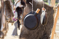 Leather flask hanging on background of animal skin Royalty Free Stock Photo