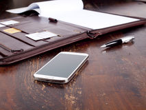 Leather folder and a modern smartphone Stock Image