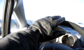Leather gloved hand on car steering wheel. Driving car Stock Photo