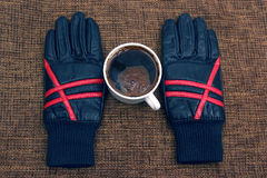Leather gloves next to a hot cup of coffee Stock Image