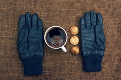 Leather gloves next to a hot cup of coffee Stock Photo