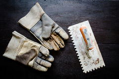 Leather gloves. Old leather gloves and rusty trowel on wooden table Stock Photos