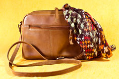 handbag and scarf. A smart tan ladies  leather shoulder bag  with a silk scarf Stock Photo