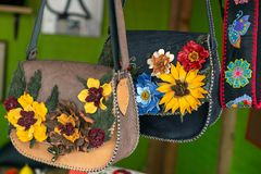 Leather Handbags with various floral decoration. And exposed to sale at one traditional fair Stock Photography