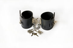 Leather handcuffs. Leather handcuffs with two padlocks and a small key royalty free stock images