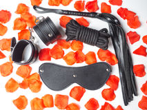 Leather handcuffs, leather whip,leather mask and black cord. On white background. BDSM Kit Stock Photo