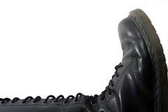 Leather jackboot. Isolated black leather jackboot lying on white background Stock Photos