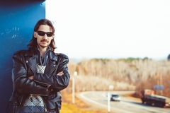 Leather jacket the road. Male biker in a leather jacket and bandana puts on sunglasses and looking at the camera. Motorcyclist in leather jacket puts on Royalty Free Stock Images