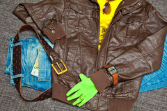 Leather jacket, T-shirt, jeans with a leather belt, watches, bracelets, sunglasses and gloves Royalty Free Stock Images