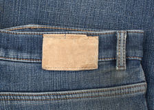 Leather jeans label sewed on a blue jeans. Blank leather jeans label sewed on a blue jeans royalty free stock photography