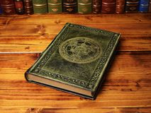 Leather journal in green color tone, gilded with ancient Alchemy symbol. Lay down to the table with the books in the background stock photography