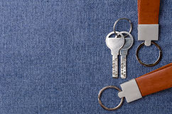Leather key chain with keys on blue fabric background Royalty Free Stock Photo