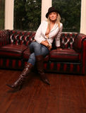 Leather Kirsty. Sexy model wearing leather boots on a leather sofa Royalty Free Stock Photos