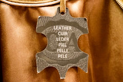 Leather label for genuine leather products. In the international shield shape with white text displayed on merchandise in a store Royalty Free Stock Photography