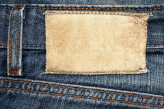 Leather label on jeans. Highly detailed closeup of blank grungy leather label on vintage dark denim, good for background Stock Photos