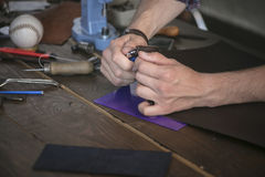 Leather maker cut leather with utility knife on wooden working table. With instrument. Neat cutting leather product in workshop. Work with dangerous tool Royalty Free Stock Photos