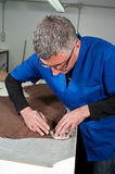 Leather manufacture. Skilled leather manufacture worker cutting some samples Royalty Free Stock Photography